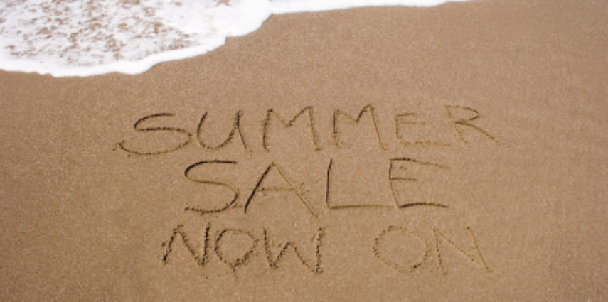 A summer sale written in the sand